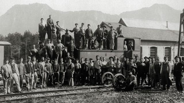 Altes schwarz-weiss Bild von einer grossen Gruppe Eisenbahnarbeitern die auf einer Lock fürs Foto posieren