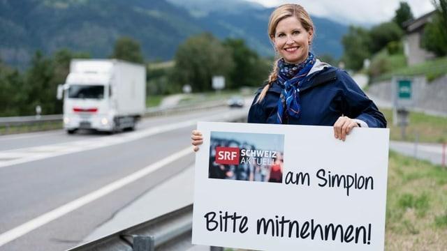 """Sabine Dahinden an einer Strasse mit einem Schild, auf dem """"<Schweiz aktuell> am Simplon - bitte mitnehmen!"""" steht"""
