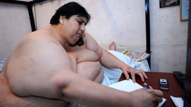 Manuel Uribe im Bett sitzend und etwas schreibend.