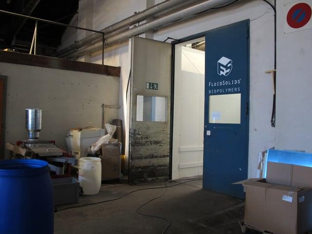 Eingangstüre mit dem Logo von FluidSolids, Grosse Plastikkübel, Gerätschaften und Kartonschachteln stehen herum.