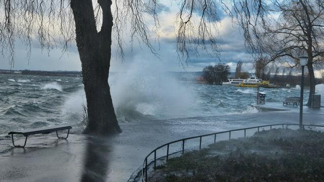 Wellen schlagen in Zug über den Uferweg.
