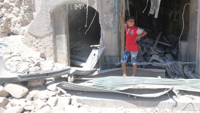 Ein Junge mit rotem T-shirt steht in einer Öffnung eines zerstörten Gebäudes.
