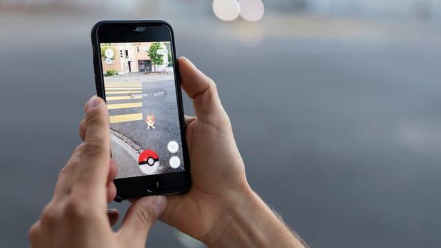 Jemand hält ein Smartphone, auf dem «Pokémon Go» gespielt wird in die Kamera.