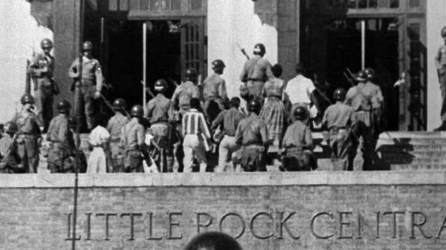 Soldaten und Schüler auf der Treppe vor dem Eingang der Little Rock Central Highschool.