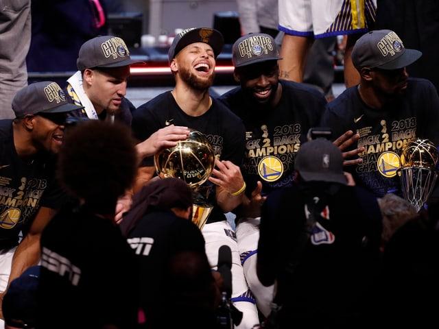 Die Golden State Warriors feiern mit der Trophäe.