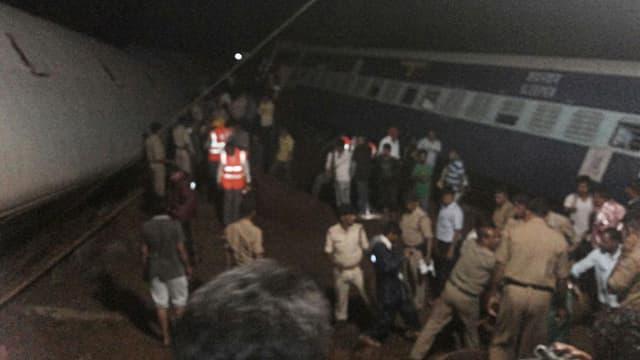 Retter bergen in der Nacht Passagiere aus einem schräg liegenden Eisenbahnwagen