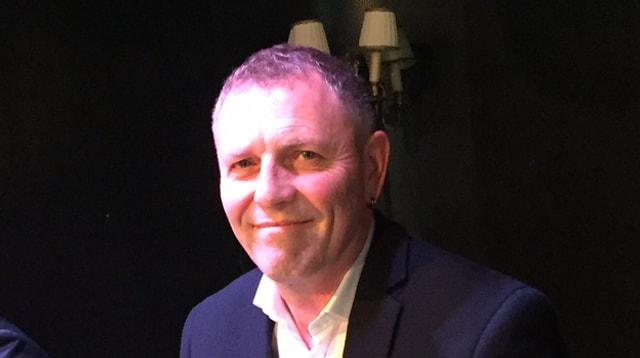 Ein Mann mit weissen Hmed und schwarzem Sacko lächelt in die Kamera.