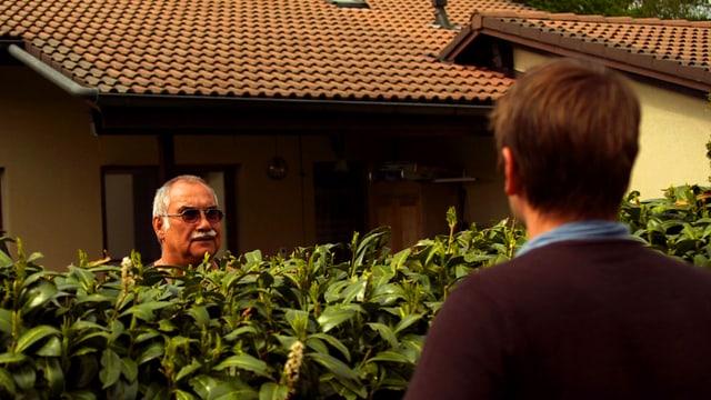 Zwei Männer schauen sich über eine Hecke hinweg an.