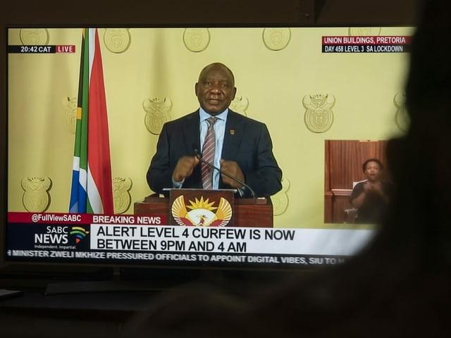 Frau schaut Rede von Ramaphosa im Fernsehen