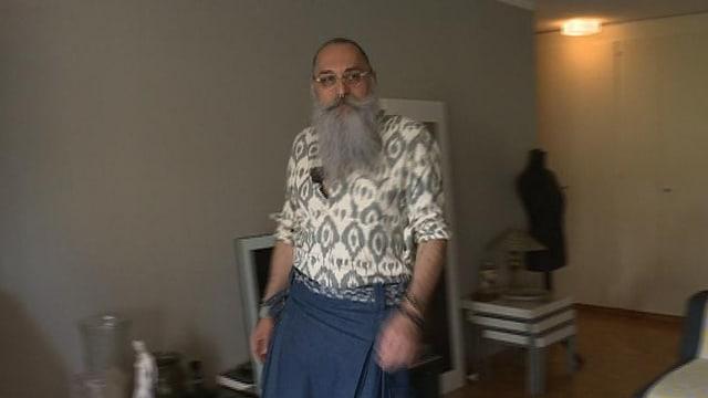Gerold Brenner hat einen grauen Vollbart und trägt einen Jeansrock.