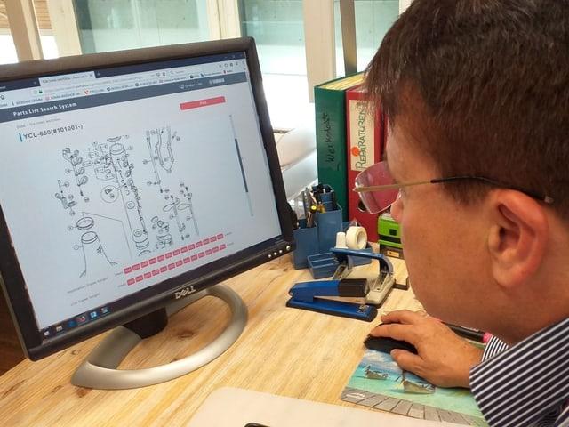 Ein Mann mit Brille vor einem Computer.