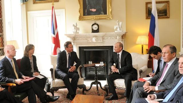 Putin und Cameron sitzend vor einem Kamin.