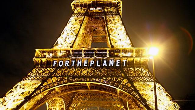 Purtret da la Tur Eiffel cun scrit si «per il planet» per engles.