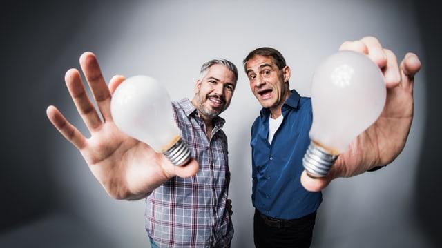 Krispin Zimmermann und Thomy Scherrer halten eine Glühbirne vor die Kameralinse.