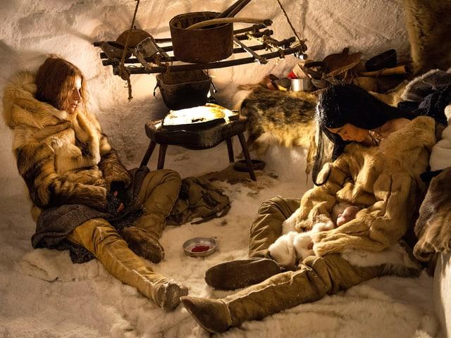 Die Frau des Polarforscherus und die Inuit sitzen in einem Iglu. Sie scheinen erschöpft. Die Inuit hält ein kleines Kind.