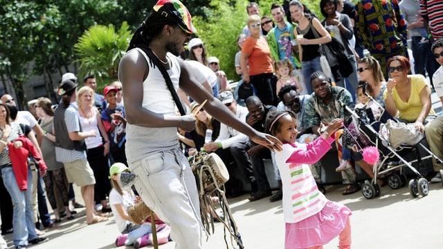 Ein kleines Mädchen tanzt mit einem Mann, der trommelt.