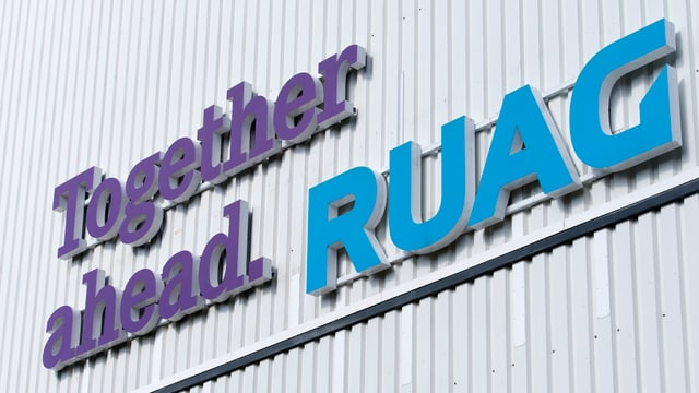 "Firmenmotto ""Together ahead - Ruag"" an der Wand eines Firmengebäudes."
