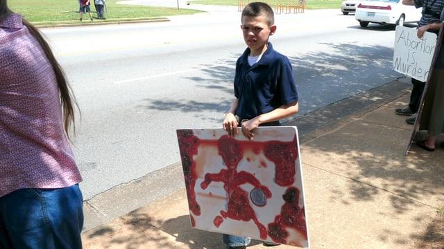 Kind mit einem Anti-Abtreibungs-Schild