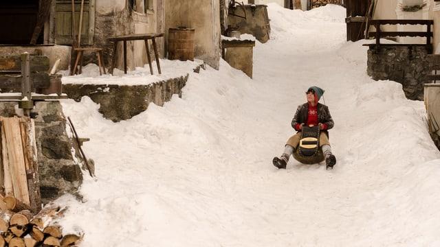 Jonas Hartmann fährt auf dem Glockenschlitten durchs verschneite Dorf.