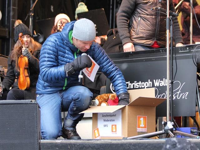 Adrian Küpfer mit Paket auf der Bühne.