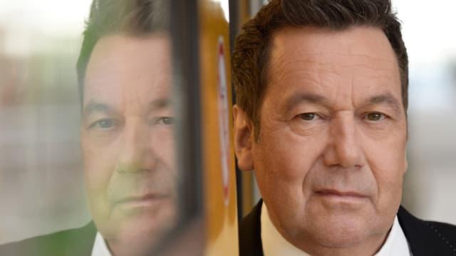 Roland Kaisers Profil spiegelt sich im Glas einer U-Bahn.