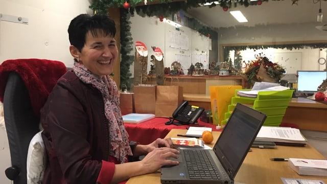 Die neue Präsidentin der St. Niklausgesellschaft, ein Frau mit dunkeln, kurzen Haaren sitzt hinter einen Laptop und lächelt in die Kamera. Das Foto wurde im Samichlausbunker aufgenommen.