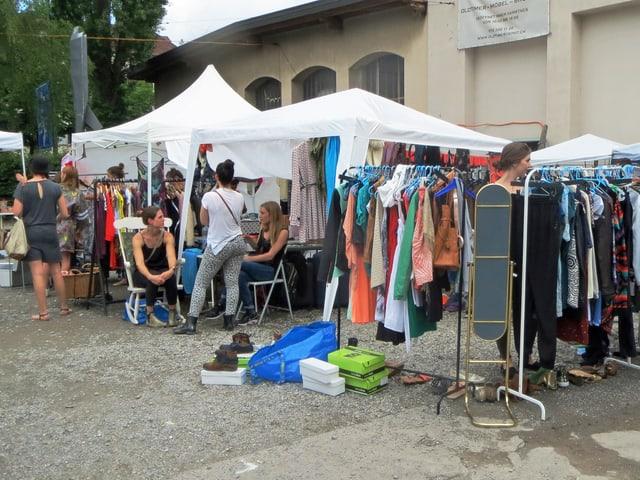 Junge Frauen durchstöbern Kleider am Flohmarkt.