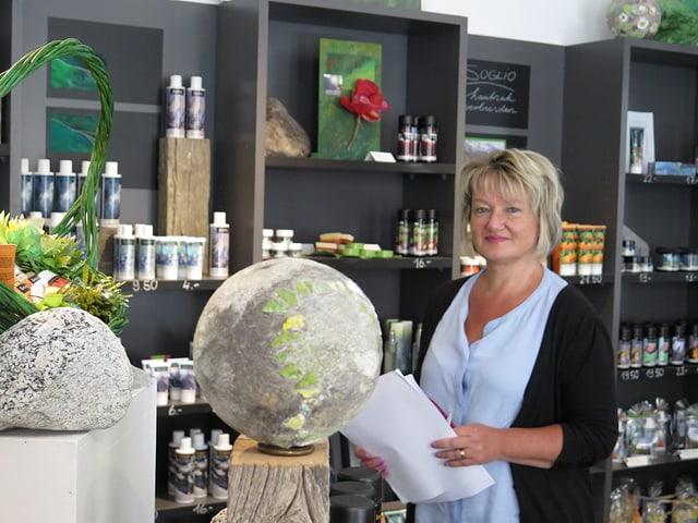 Eine Frau steht in einem modernen Geschäft, hinter ihr sieht man Shampoo-Flaschen