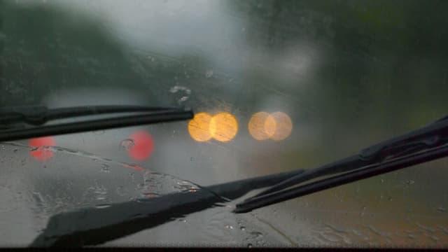 Scheibenwischer an der Frontscheibe eines Autos an einem verregneten Tag.