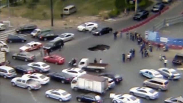 Auto fällt in ein Loch in der Strasse