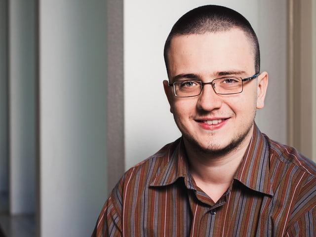 Ein junger Mann mit Brille lächelt in die Kamera.