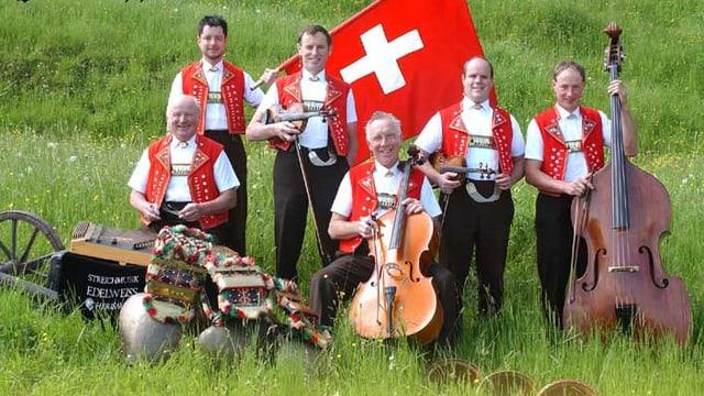 Männer in rot-weissen Appenzellertrachten stehen oder sitzen mit ihren Instrumenten auf einer Wiese.