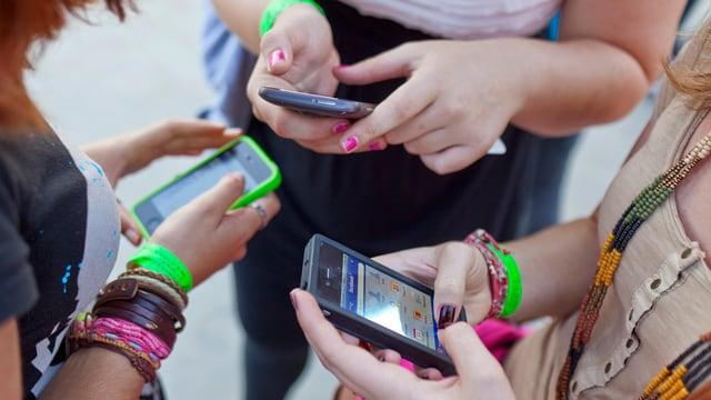 Symbolbild: Man sieht die Hände von drei jungen Frauen, die mit ihren Smartphones hantieren.