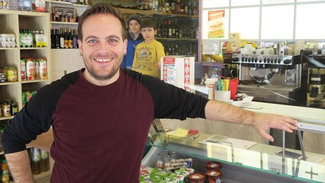 Ein Mann steht in einem Lebensmittelladen - im Hintergrund stehen zwei Kinder.