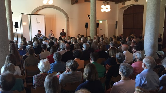 Ernst Halter diskutiert in einem grossen und gut besetzten Saal über das Thema «kürzen».