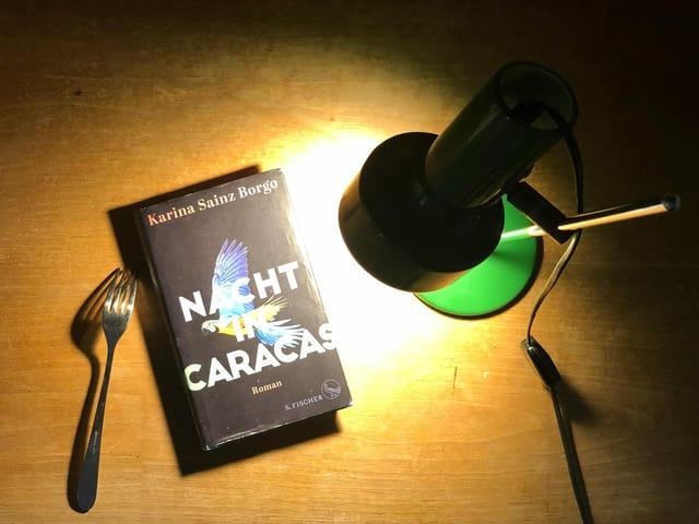 Der Roman «Nacht in Caracas» liegt im Lichtkegel einer Tischlampe