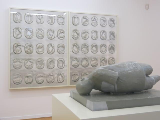 Eine Skulptur im Vordergrund, im Hintergrund eine Fotografie an einer Wand.