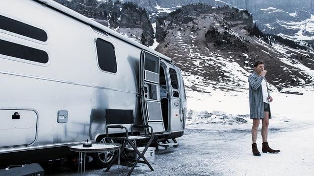 Ein Mann steht neben einem Wohnwagen in einer verschneiten Landschaft. Er putzt sich die Zähne, trägt nur einen Bademantel, darunter Boxershorts.