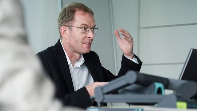 Der Zürcher Finanzvorstand Daniel Leupi erklärt sitzend und mit erhobener Hand das Budget 2014.