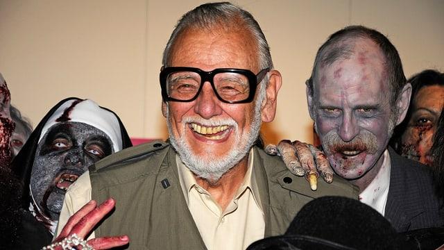 George A. Romero umgeben von Zombies.