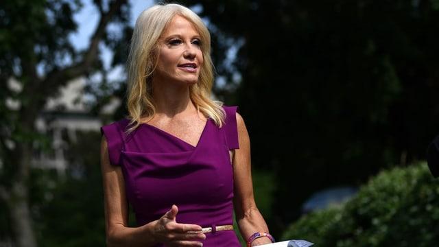 Conway spricht in einem violetten Kleid zu Reportern.
