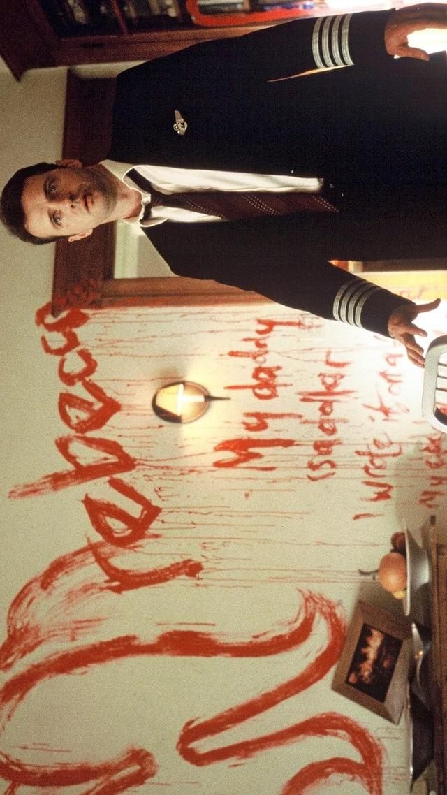 Mann ist schockiert - im Hintergrund blutverschmierte Wand