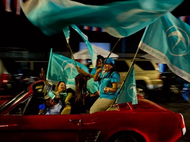 Anhänger der Gana-Partei mit Fahnen in einem Auto