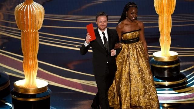 Mann und Frau in Abendkleidung auf einer Bühne vor grossen Goldstatuen er hält einen roten Umschlag in der Hand.