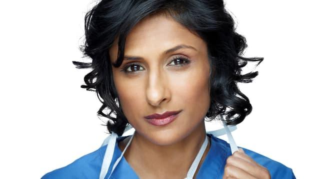 Eine dunkelhäutige Frau im blauen Ärztekittel.