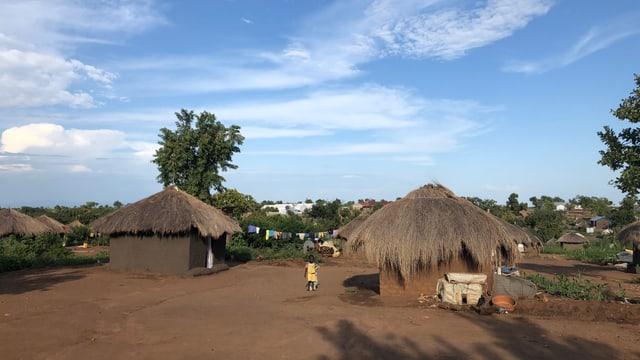 Hütten mit Strohdach, blauer Himmel, Kind läuft auf braunem Boden.