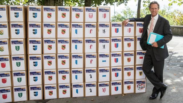 Nationalrat Christian Lüscher (FDP/GE) posiert neben den Schachteln mit den Unterschriften.
