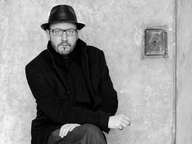 Porträt eines Mannes mit schwarzem Mantel und Hut.