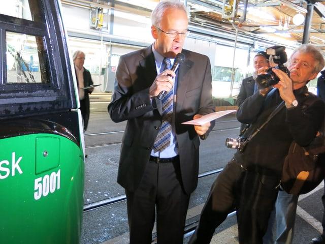 """Erich Lagler steht vor dem Bug eines neuen Flexity-Trams mit der Aufschrift """"Basilisk"""" und spricht in ein Mikrophon. Neben ihm steht ein Mann, der ihn fotografiert."""