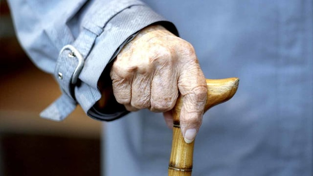 Eine alte Frau hält einen Stock in der Hand.